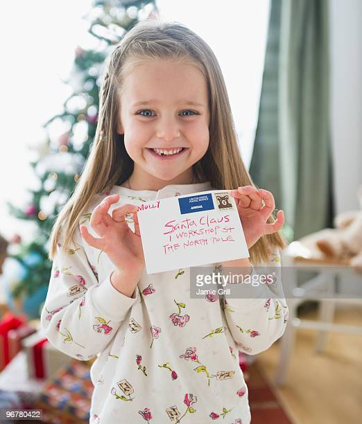 Young girl holding letter addressed to Santa Claus