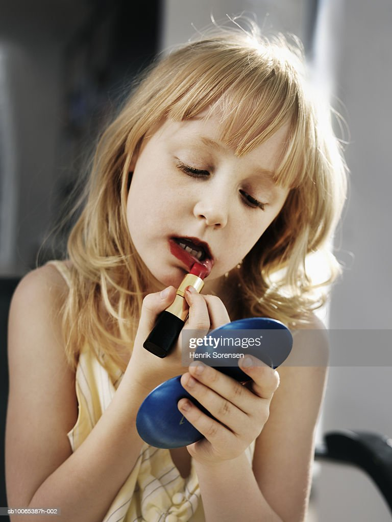 Young girl (6-7) holding mirror and applying lipstick : Foto stock