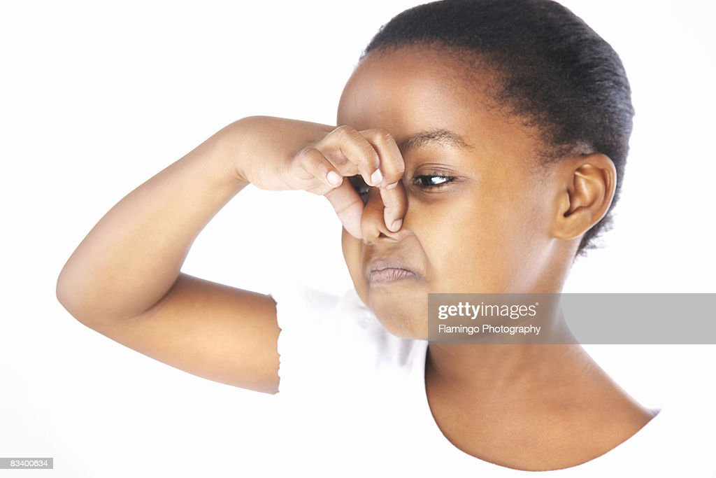 Young girl holding nose : Stock Photo