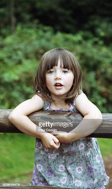 Young girl holding on to wooden barrier