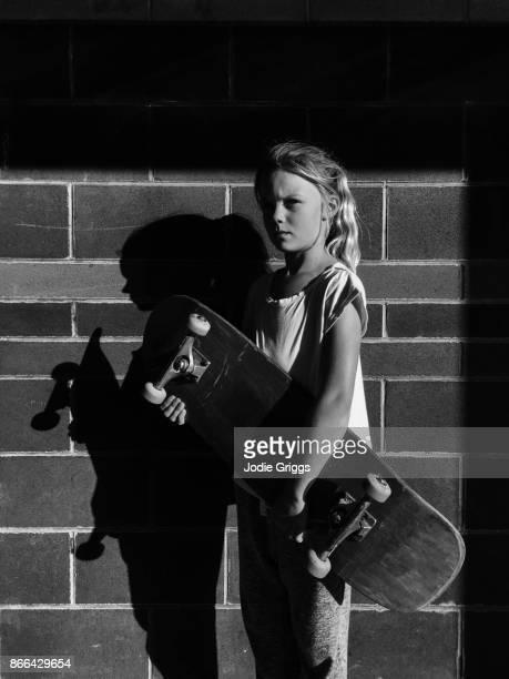young girl holding onto a skateboard - ein mädchen allein stock-fotos und bilder