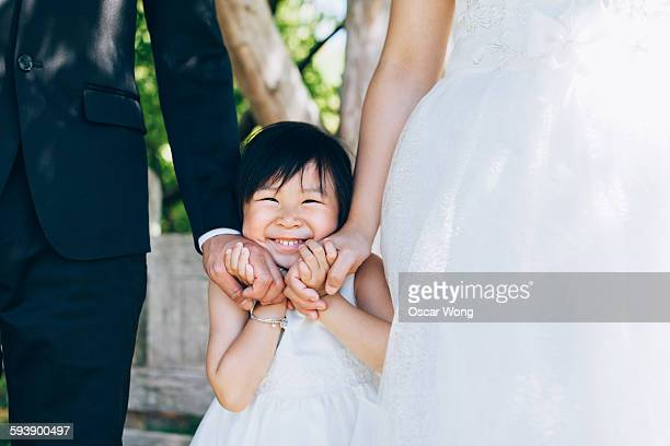 Young girl holding parents' hands on her cheek
