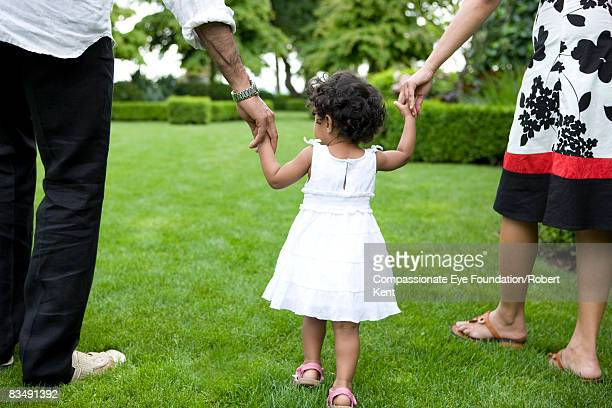 Young Girl holding parents hands.