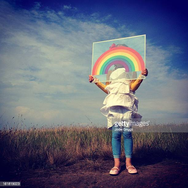 Young girl holding rainbow in front of face
