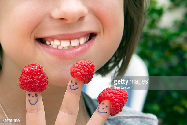 Young girl holding raspberries on her fingers