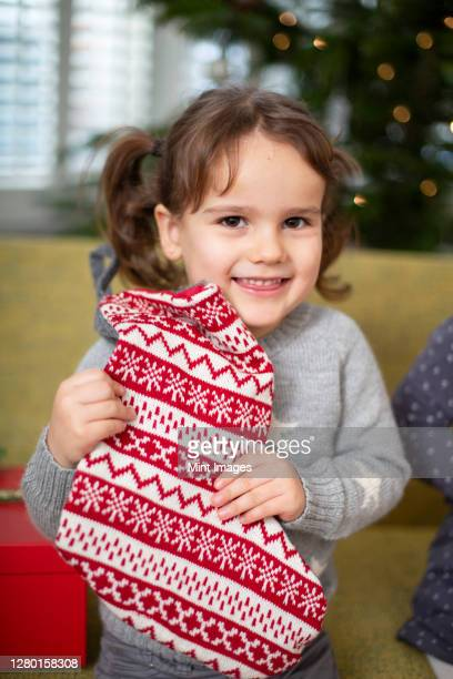 young girl holding red and white christmas stocking, smiling at camera. - stockings photos stock pictures, royalty-free photos & images