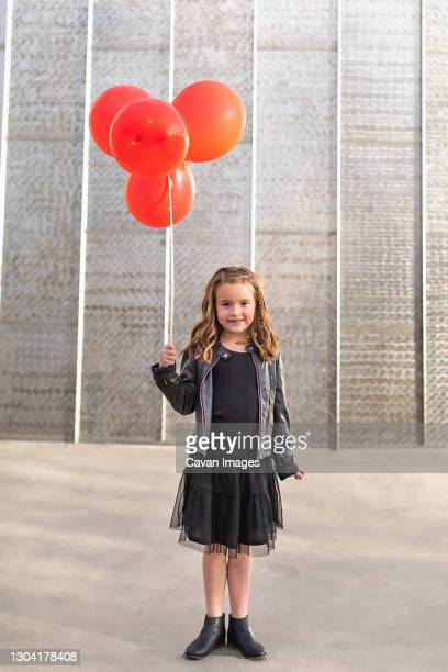young girl holding red balloons in front of a metal wall. - silver boot stock pictures, royalty-free photos & images