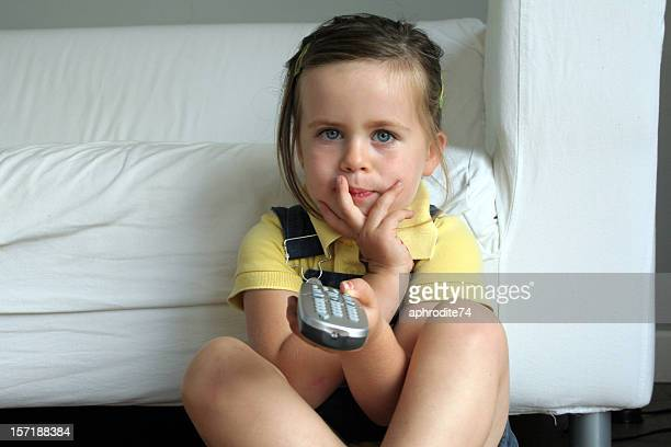 Young girl holding remote and watching television