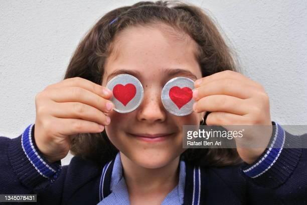 young girl holding round hearts symbols on her eyes - rafael ben ari fotografías e imágenes de stock