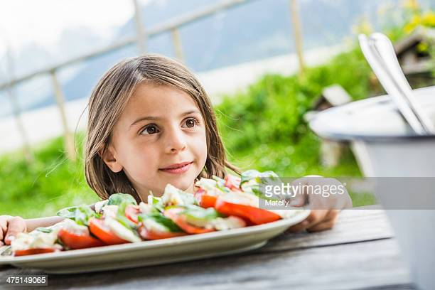 Young girl holding salad plate for picnic lunch, Tyrol, Austria