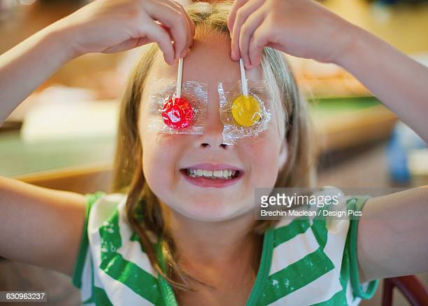 Young girl holding suckers over her eyes: Richmond, British Columbia, Canada