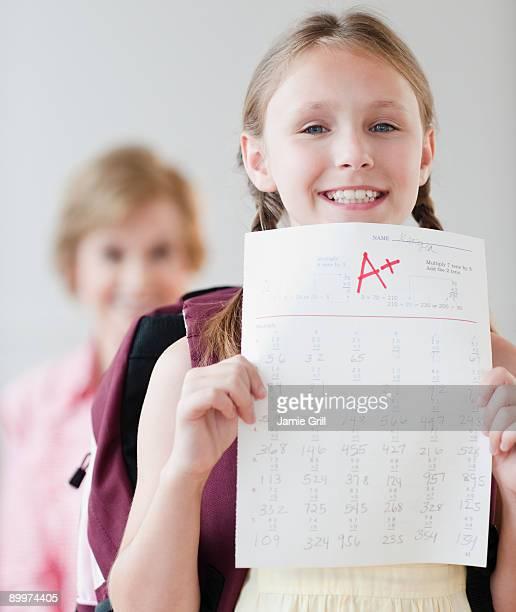 young girl holding test with a+ grade - boletim escolar imagens e fotografias de stock