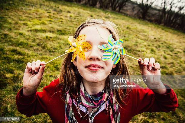 young girl holding two windmills - arti e mestieri foto e immagini stock