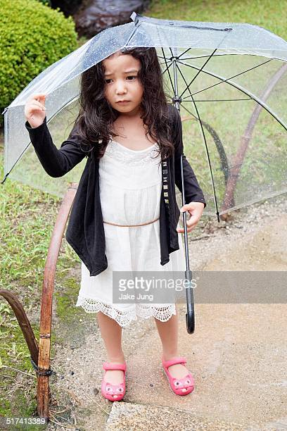 Young girl holding umbrella in the rain