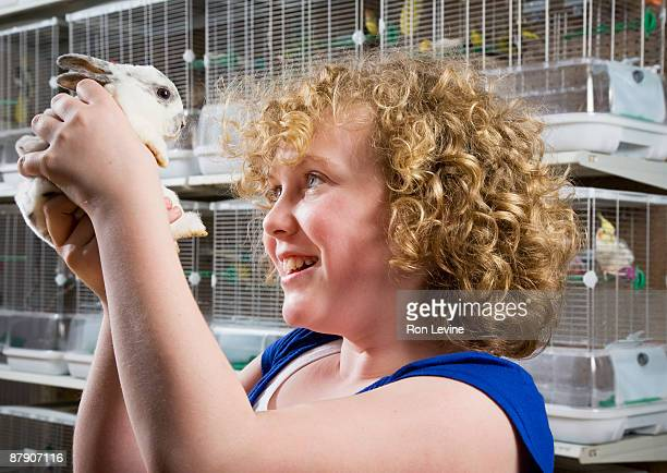 Young girl holding up a baby bunny in a pet shop
