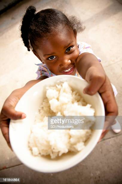 Young girl holding up a bowl of rice