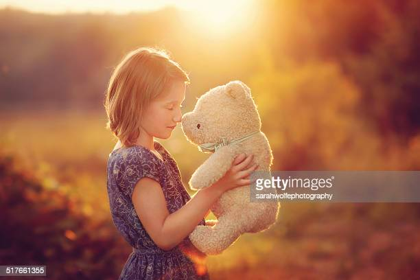 Young girl holding up her teddy bear in sunshine