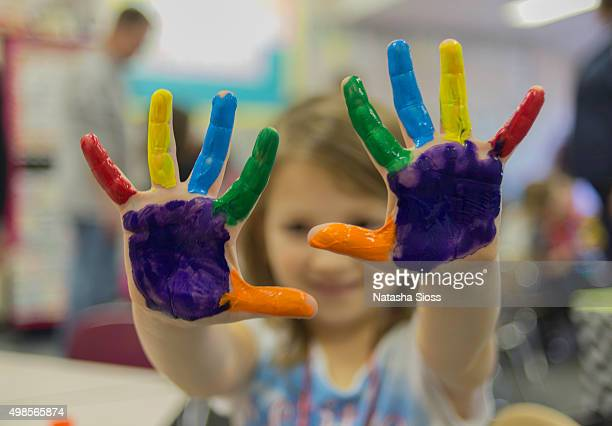 Young girl holding up painted hands