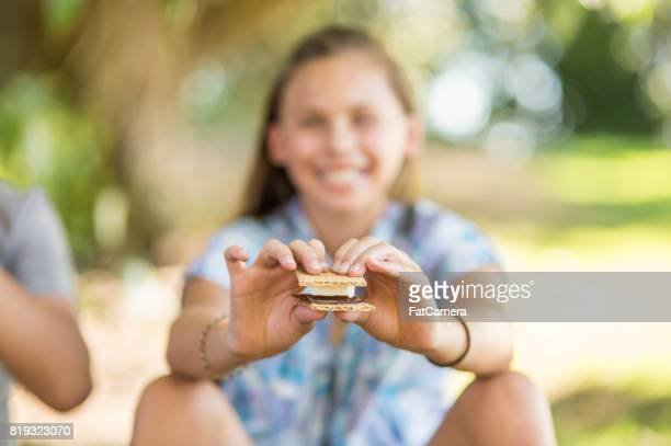 Young girl holding up s'more she's just made