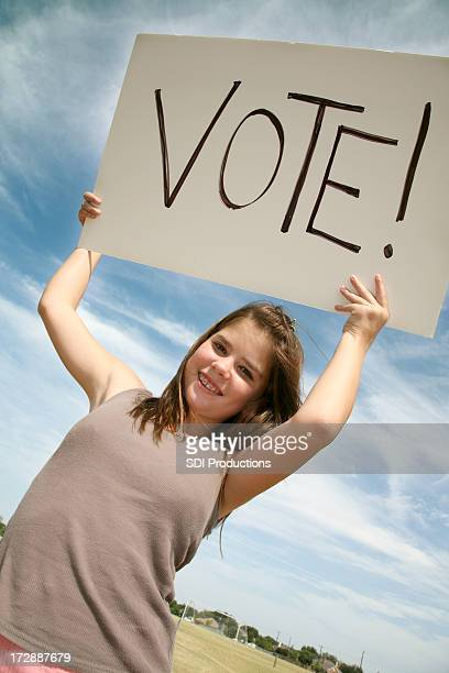 Young Girl Holding Vote Sign In The Air Outside