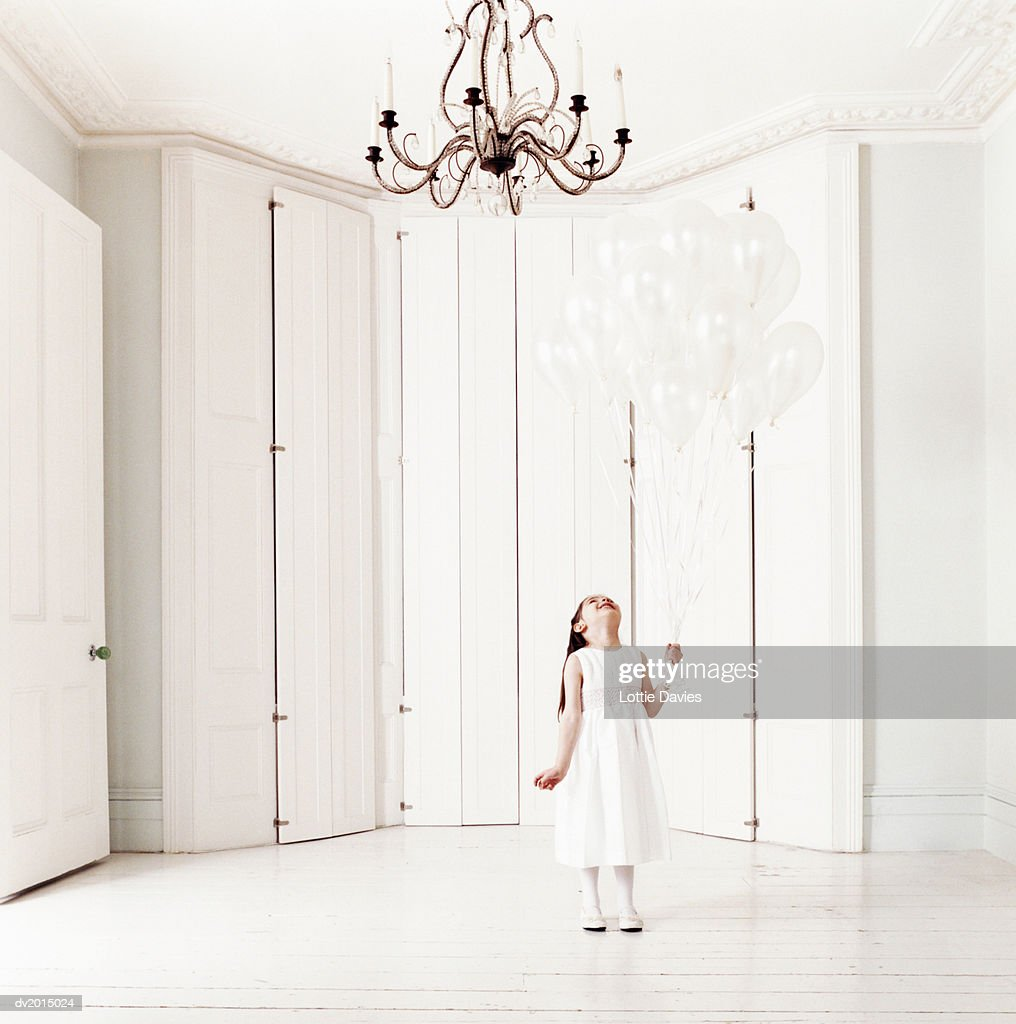 Young Girl Holding White Balloons Looking Up at a Chandelier : Stock Photo