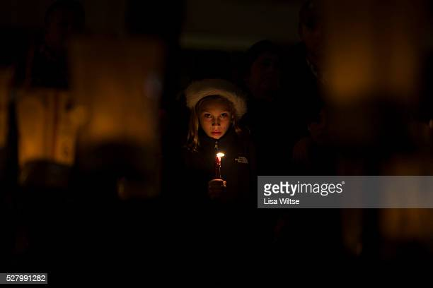 A young girl holds a candle at a townwide community vigil on Sherman Green in Fairfield Connecticut after the mass shootings at Sandy Hook Elementary...