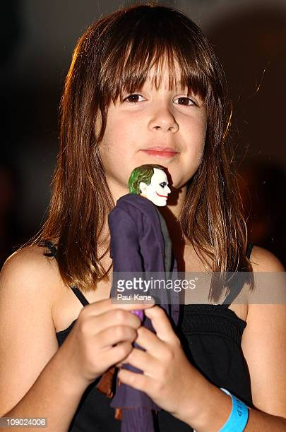 A young girl holds a figurine of the Joker during a public Heath Ledger tribute outdoor movie night at Burswood Park on February 12 2011 in Perth...