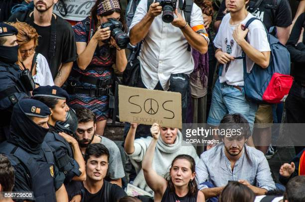 A young girl holds a poster with the text SOS DEMOCRACIA between police and demonstrators A large number of people are sitting at the headquarters of...