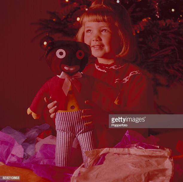 A young girl holds a present of a golliwog toy doll whilst sitting in front of a christmas tree circa 1963