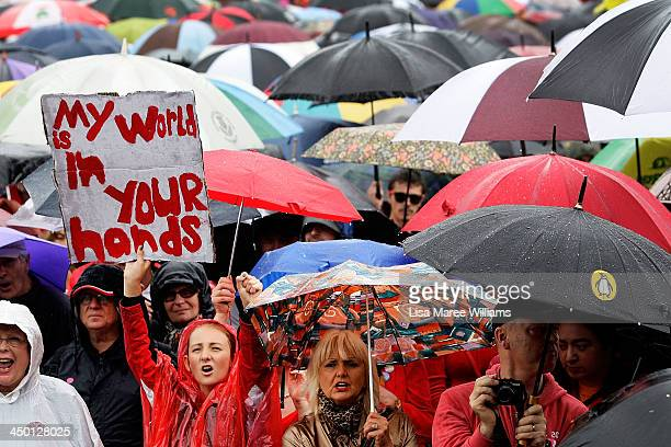 A young girl holds a protest sign in the rain during a climate change rally at Prince Alfred Park on November 17 2013 in Sydney Australia Australians...