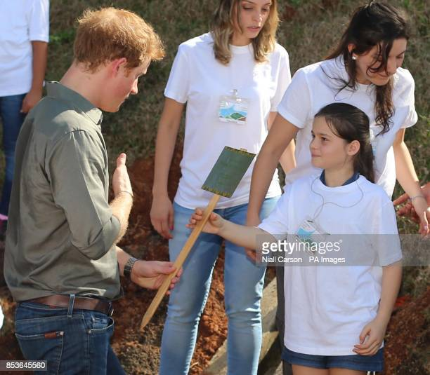 A young girl holds a sign saying Prince Henry De Gales as Prince Harry plants a tree at Cota 200 outside Sao Paolo where he viewed Mata Atlantica the...