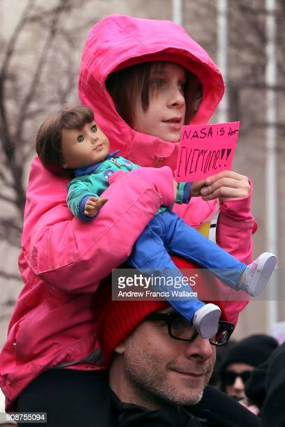 TORONTO ON JANUARY 20 A young girl holds a small sign while holding a doll during the Toronto Women's March on Bay St January 20 2018