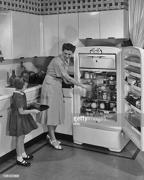 A young girl holds a tray with glasses of juice on it as her mother puts a bottle back in the open fridge circa 1950