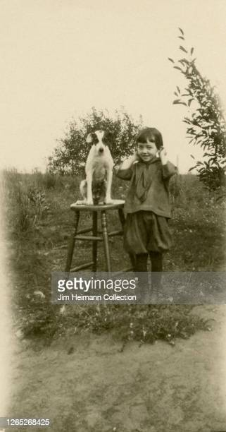A young girl holds her ears while posing for a picture with her dog which sits on a stool circa 1919