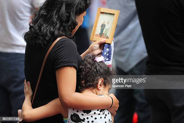 A young girl holds her mother during a commemoration ceremony for the victims of the September 11 terrorist attacks at the National September 11...