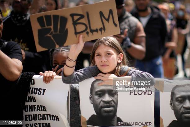 """Young girl holds up a """"BLM"""" sign during a Black Lives Matter rally in Millennium Square on June 14, 2020 in Leeds, England. Black Lives Matter..."""
