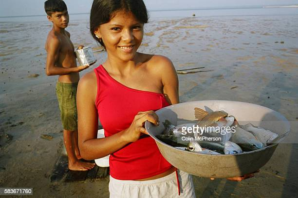 A young girl holds up a bowl of freshly caught fish from the Tapajos river in the Amazonian basin Villagers along the freshwater river lived from...