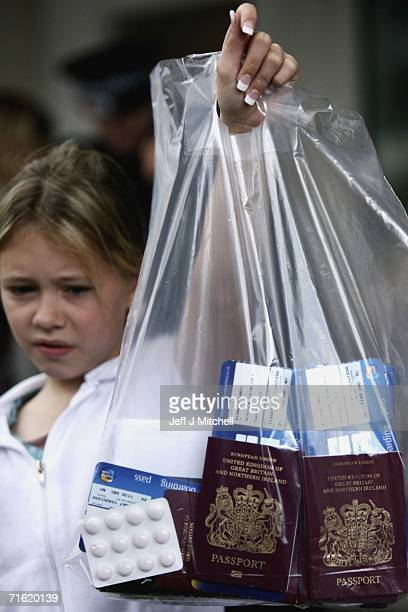 A young girl holds up a plastic bag containing the family passports and boarding cards at Glasgow Airport on August 10 2006 in Glasgow Scotland...