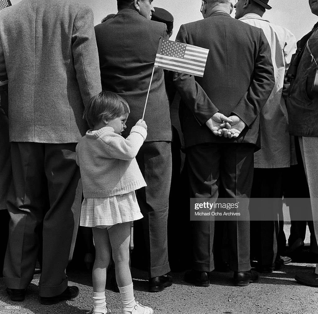 A young girl holds up an American flag at the Rudolph Wilde Platz for President John F. Kennedy's famous 'Ich bin ein Berliner' speech on June 26, 1963, in Berlin, West Germany.