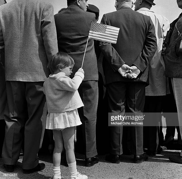 A young girl holds up an American flag at the Rudolph Wilde Platz for President John F Kennedy's famous 'Ich bin ein Berliner' speech on June 26 in...