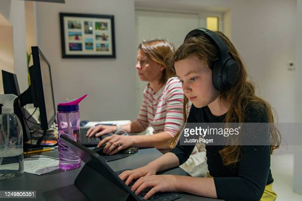 young girl home schooling whilst mother is working from home - surfing the net stock pictures, royalty-free photos & images