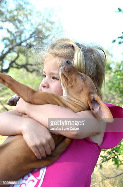 young girl hugging a puppy dog outdoors - lynn pleasant stock pictures, royalty-free photos & images