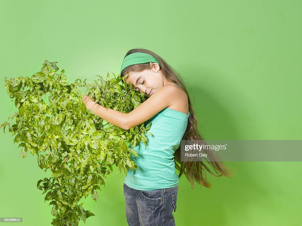 Young girl abrazándose verde bush : Foto de stock