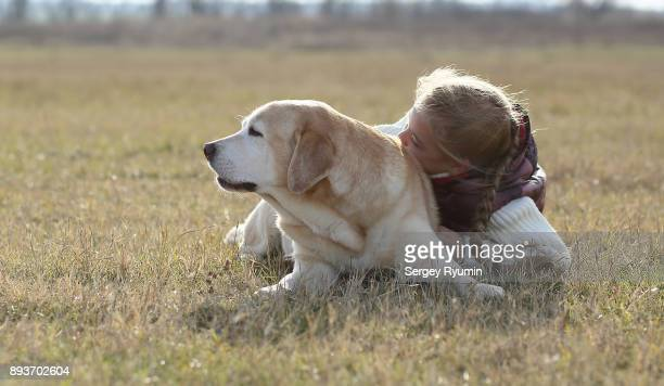 Young girl hugging her dog.