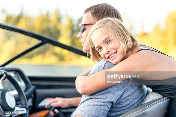 Young girl hugging her father from behind