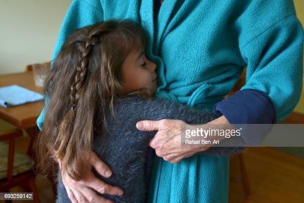 young girl hugging her grandmother - rafael ben ari stock-fotos und bilder