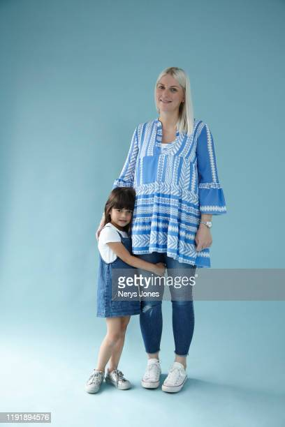 young girl hugging mother against pale blue background - nerys jones stock photos and pictures