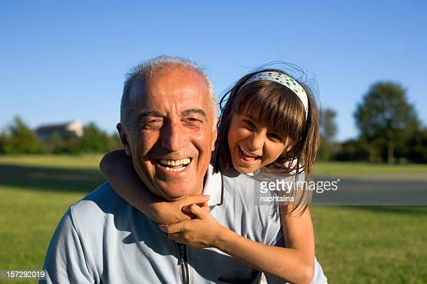 Young girl hugging older man during happy day at the park
