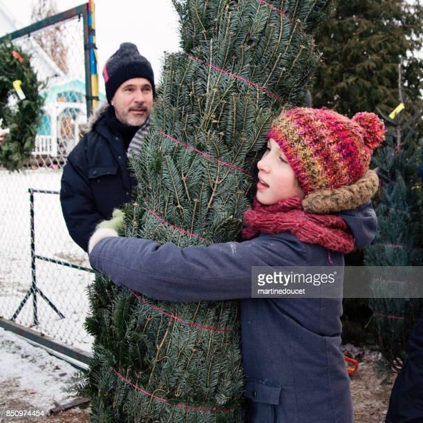 Niña abrazando el árbol de Navidad solicitado al aire libre.