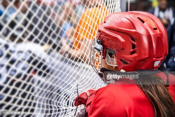 young girl ice hockey player in red equipment - difensore hockey su ghiaccio foto e immagini stock
